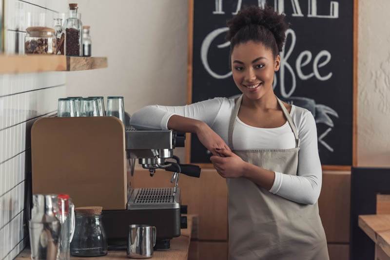 Beautiful Afro American barista in apron is looking at camera and smiling while leaning on the coffee machine